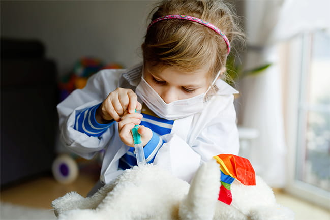 Child plays doctor with stuffed animal