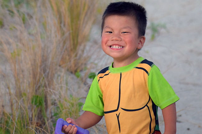 Image of child on sandy dunes smiling