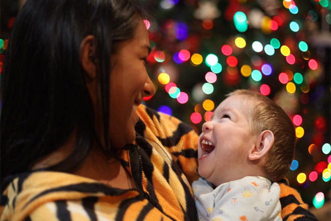 Image of mother and child in front of festive lights