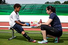 image of person tending to a soccer player's injured leg