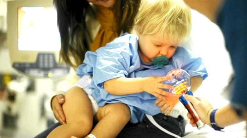 image of child in the lap of a caregiver playing with a toy