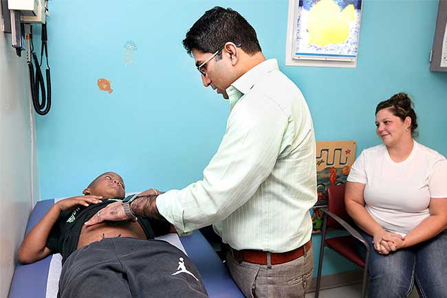 Dr. Satish Nadig checks Gabe Cade's liver while the boy's mother watches.