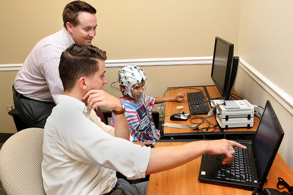 Hayes de Arellano gets to see science in action during an EEG, where Dr. Casey Calhoun (standing) and research coordinator Jesse Walker show the eight-year-old boy how the scan works.