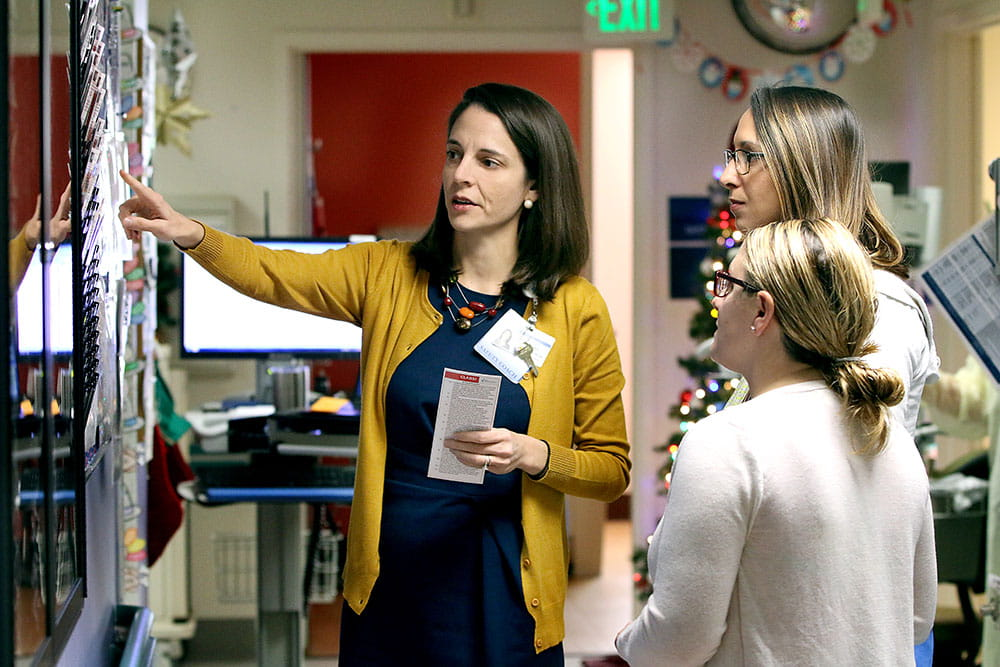 Dr. Elizabeth Mack, left goes over patient safety data with nurse Kelly Carbone, middle, and pharmacist Jennifer Santamaria.