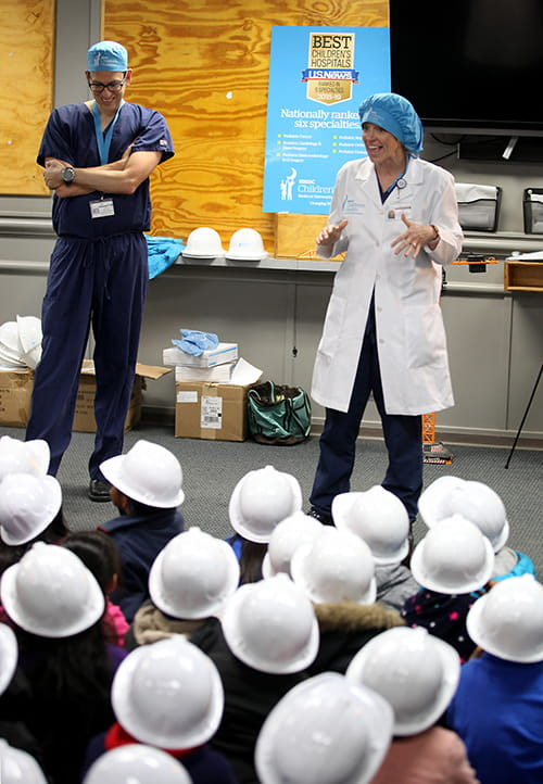 Dr. Robert Cina and PA Helen Kulseth stand in front of a group of small children wearing plastics hard hats and seated on the floor