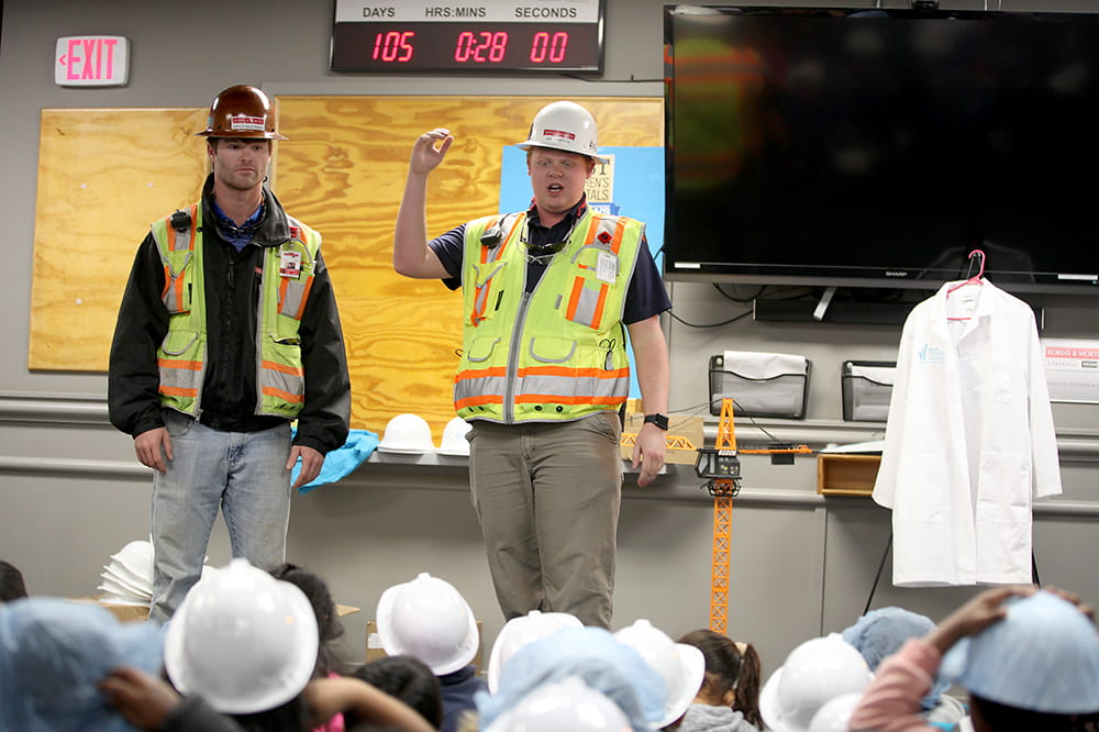 two construction workers in safety gear talk to a group of children seated on the floor