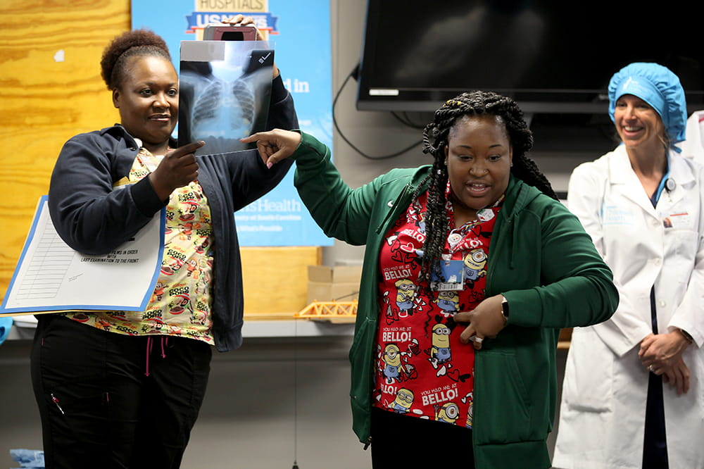 two women hold up a x-ray of a child's chest to show a group of visiting kindergartners