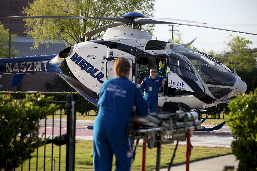 Flight paramedics bring a patient to MEDUCARE One.