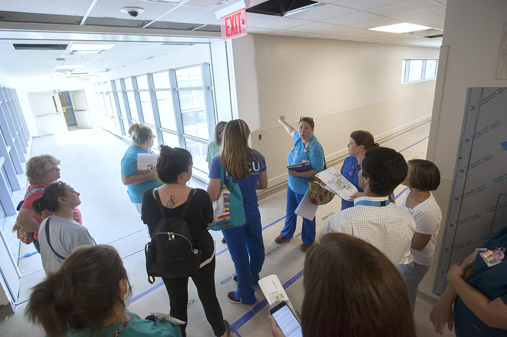 A group stands in the hallway of the not-yet-finished hospital. Brown paper is taped to the floor. Many of the people hold maps.