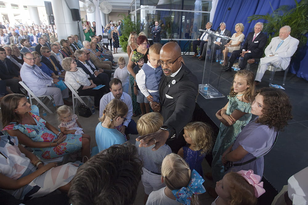 A man in traditional black pastor's suit holds a little boy wearing a suit and vest and is surrounded by small children