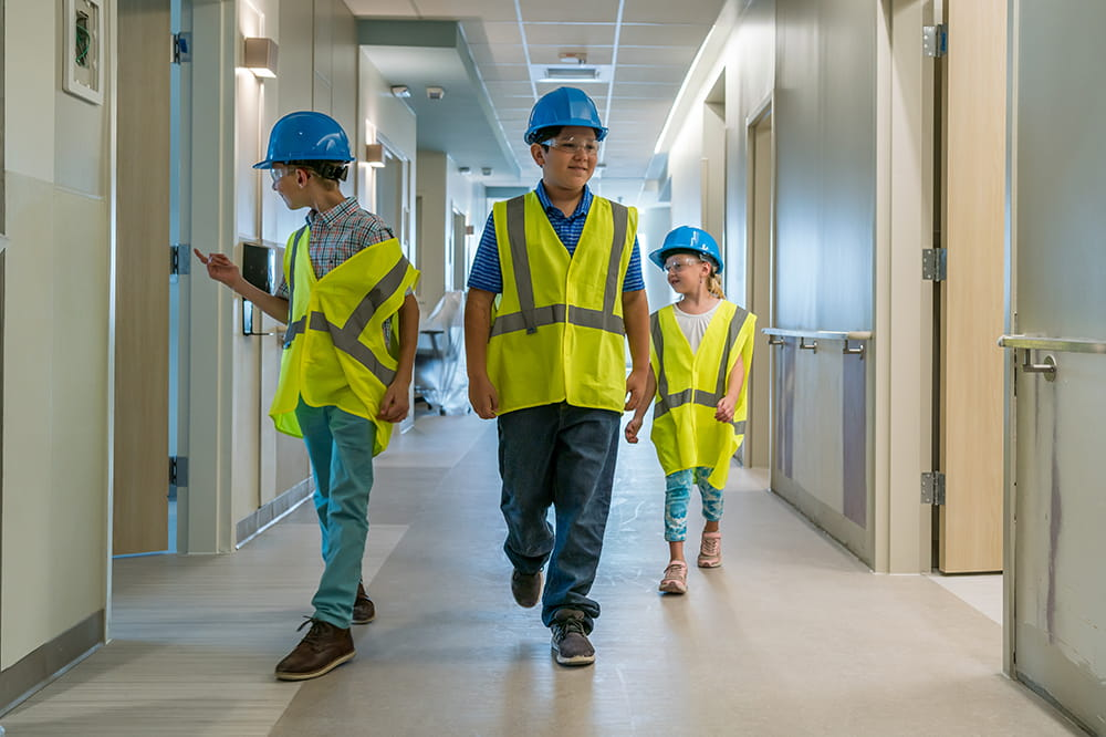 three children in hard hats and adult-sized yellow vests walk through the halls of the nearly-complete hospital