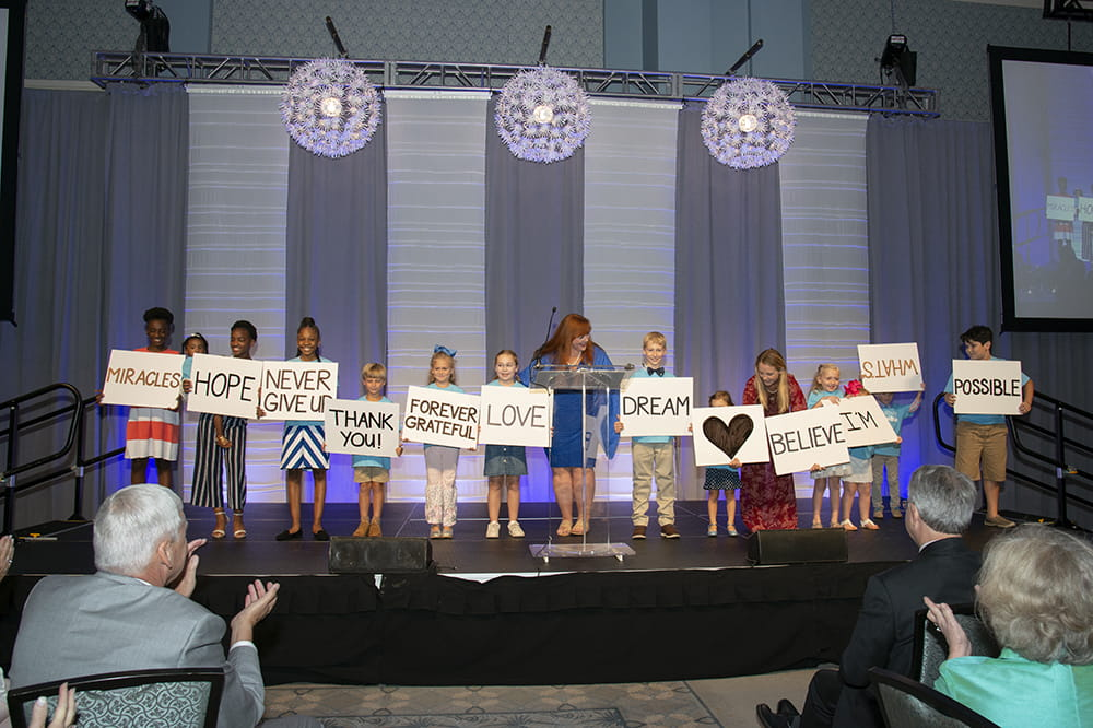Current and former patients stand on a stage and hold up signs with messages like Hope, Love and Forever Grateful.