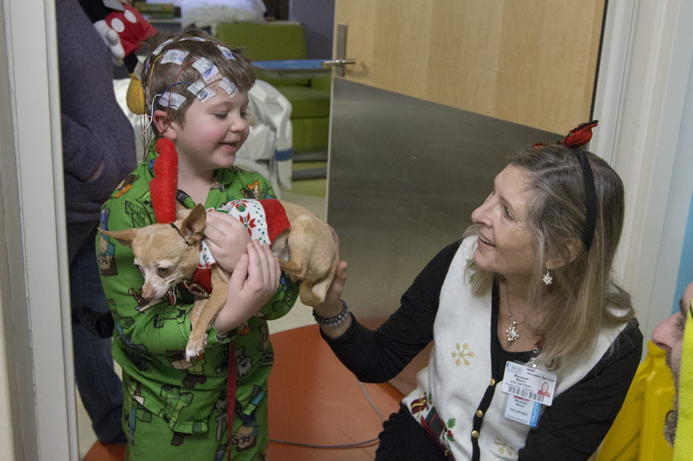 "Five-year-old Sullivan Cole holds Fierce, aka ""Max,"" as Marybeth Myers and the Grinch look on. Photos by Sarah Pack"
