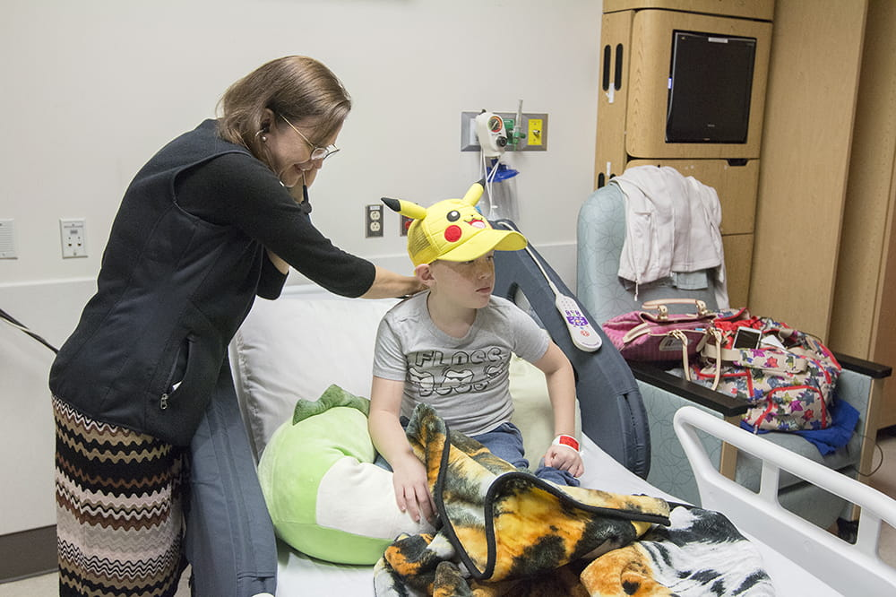 A doctor uses a stethoscope to listen to a young boy's breathing as he sits in his hospital bed wearing a Pokemon hat.