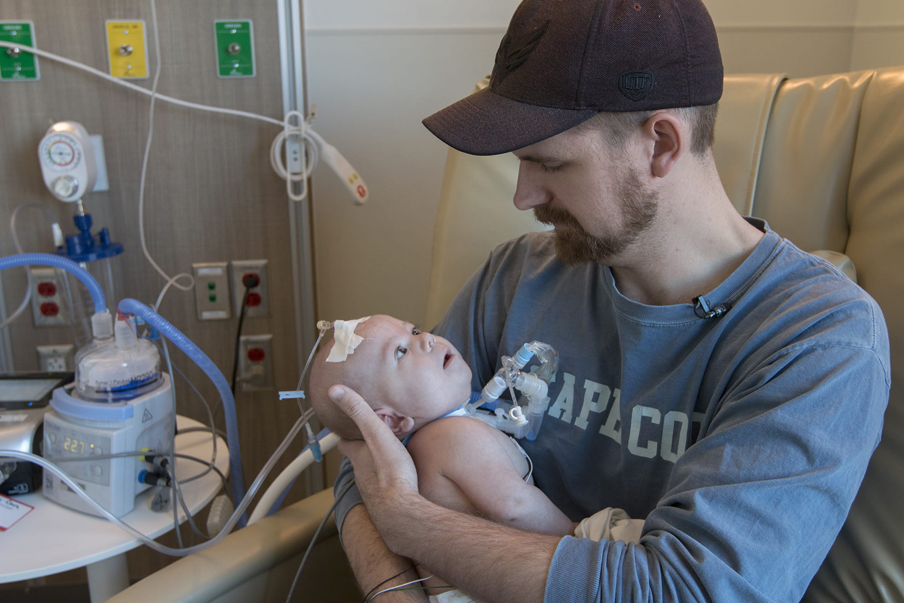 man holds his infant son in hospital
