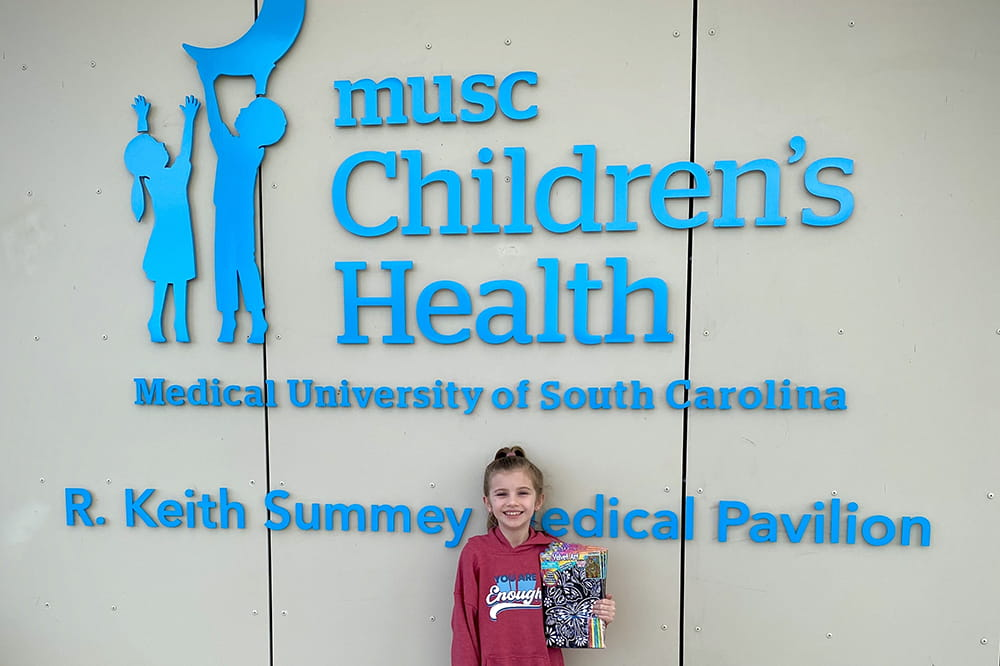 girl stands in front of the sign on the Summey Medical Pavilion