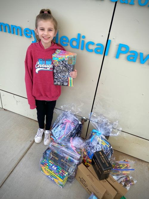 A girl stands in front of the Summey Pavilion with art kits