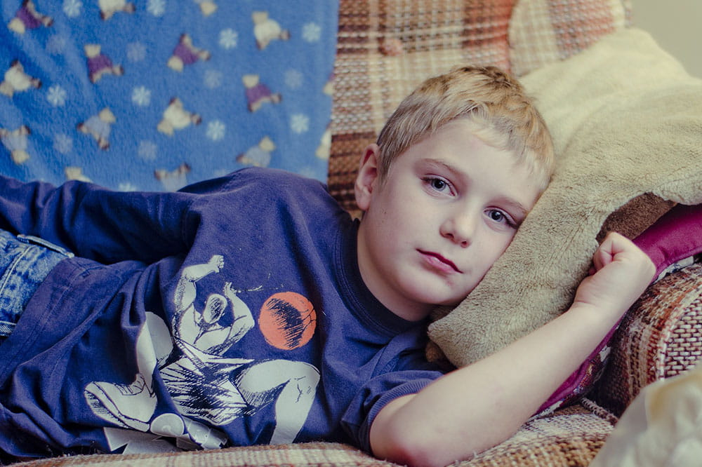 Boy lying on sofa
