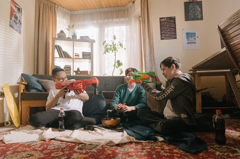 three tween boys sit on the floor of a family room, with two boys playfully pointing toy water guns at each other