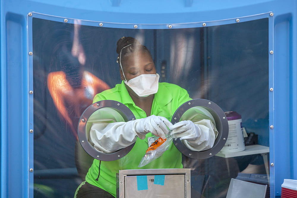 a woman sits inside the blue shell of a portable toilet, wearing a mask over her nose and mouth, reaching her arms through built-in gloves to hold a specimen collection bag