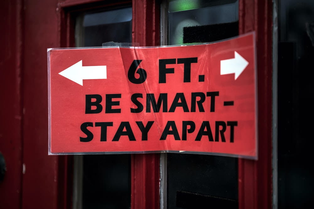 sign saying six feet, be smart, stay apart