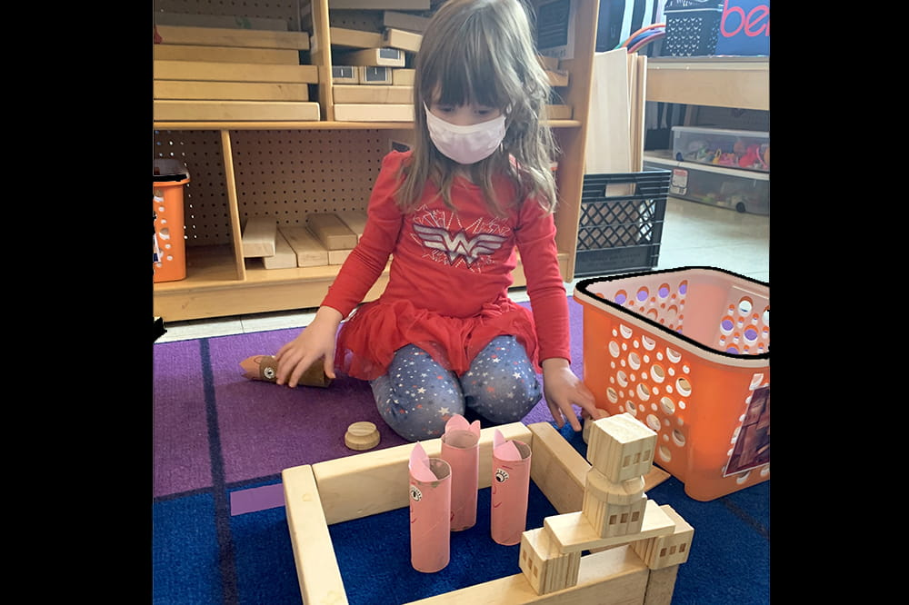 Girl wearing a mask plays with blocks.