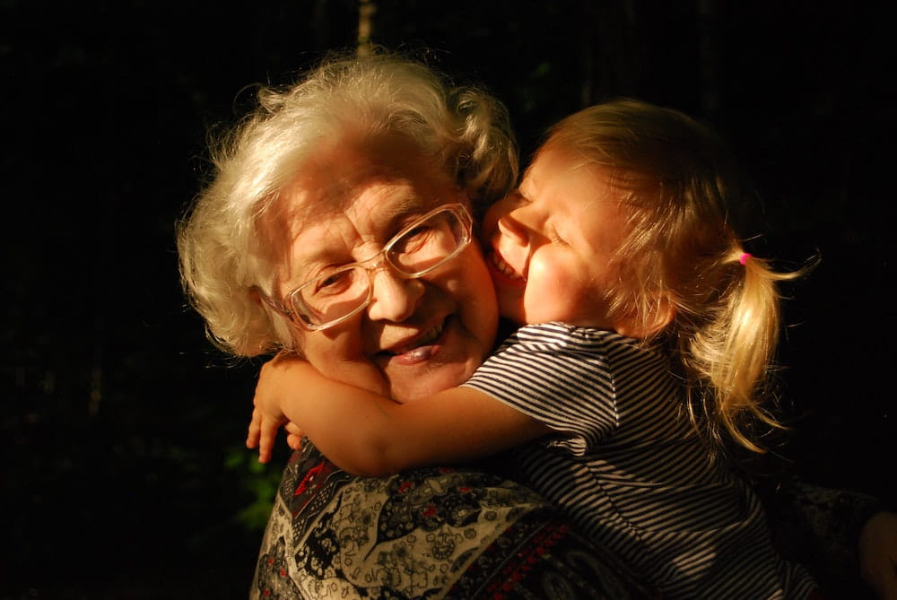 A grandmother being hugged by her granddaughter
