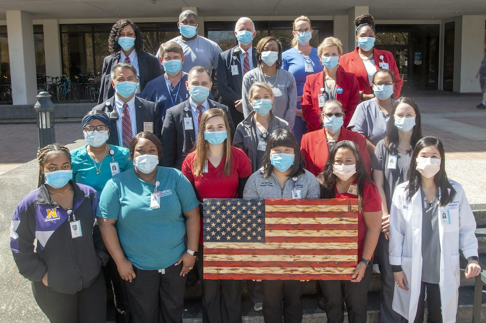 A group of about 20 health care employees standing outside behind a hand carved wooden American flag